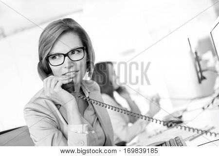 Young businesswoman talking on telephone at desk in office