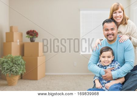 Happy Mixed Race Family with Son in Room with Packed Moving Boxes.