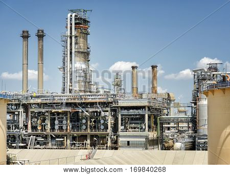Oil Refinery With White Clouds And Blue Sky