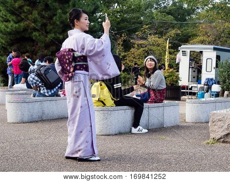 Kyoto, Japan - September 30, 2015: Young girl in colorful kimono taking pictures with smartphone in Maruyama park