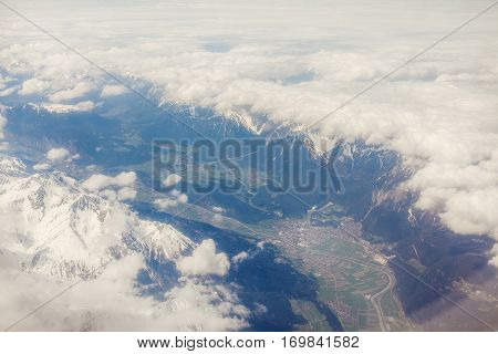 Aerial view of clouds and village landscape. Earth viewed from airplane under white clouds. Road among mountains