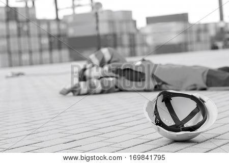 Yellow hardhat at shipyard with depressed male worker lying in shipping yard