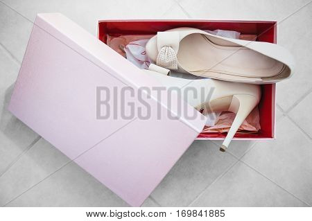 Wedding shoes in a box. White new high heeled leather shoes packed into box. Luxury footwear for bride. Two elegant bridal dress shoes in package on floor made of ceramic tile. Stylish accessory