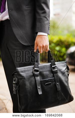 Leather suitcase in man's hand. Person in suit holding elegant men's bag. Fashion accessory for males, travel suitcase