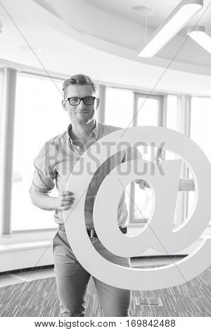 Portrait of creative businessman holding at sign in office