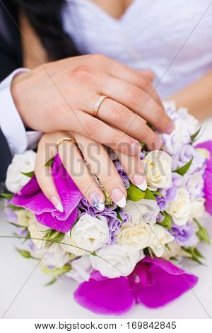 Wedding rings on couple hands on bridal bouquet. Engagement rings on just married bride and groom hands. Golden female and male rings. Jewelry accessory for wedding day. Symbol of eternal love