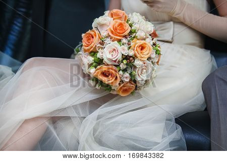 Bridal bouquet with orange and white roses lying on knees of bride. Fiancee in wedding dress sitting in car. Romantic wedding bouquet with beautiful flowers. Elegant round bunch of fresh roses.