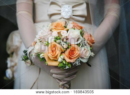 Bride in gloves stands in white dress with bow on waist holds bridal bouquet with roses. Wedding bunch of fresh flowers with orange and beige roses of different size. Romantic accessory of fiancee