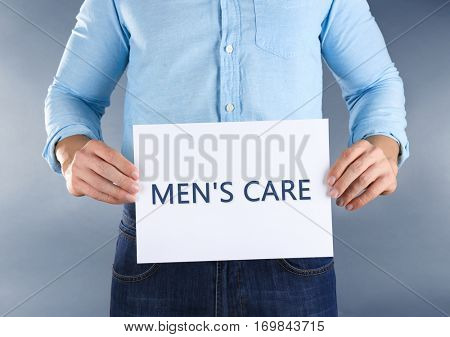 Man holding paper with text MEN'S CARE, closeup. Health care concept.