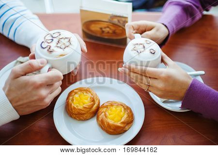 People drinking coffee in cafe, closeup of couple hands with cups. Tasty biscuits on white plate. Breakfast or lunch in restaurant. Delicious cappuccino with foam. Hot aromatic drink in hands
