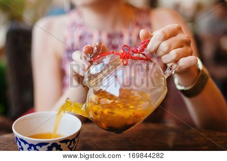 Female hands pouring sea buckthorn tea in glass kettle into ceramic cup. Unrecognizable girl with hot beverage. Herbal tea in transparent tea kettle. Refreshment aromatic drink in tea pot in girl hand