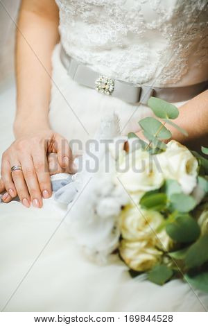Bride sitting with crossed hands in wedding ring and bridal bouquet near her. White dress with bow on waist. Wedding bunch of fresh flowers, romantic accessory of fiancee. Excellent manicure on nails