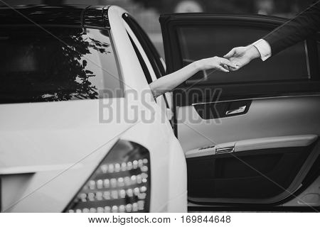 Bride in luxury car gives hand to bridegroom in white and black colors. Just married wife gets out of auto elegant man helps her stretching his hand. Tenderness ladies arm holding males arm poster