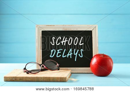 Small blackboard with text SCHOOL DELAYS and notebook on blue wooden table