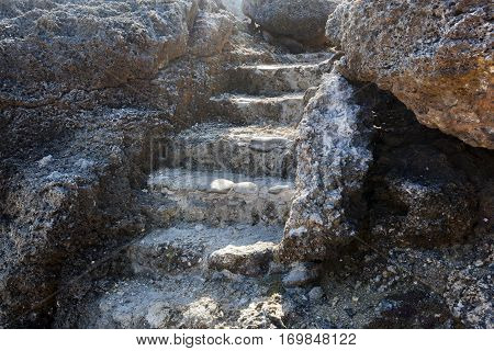Old staircase in volcanic rock near a bay on Curacao