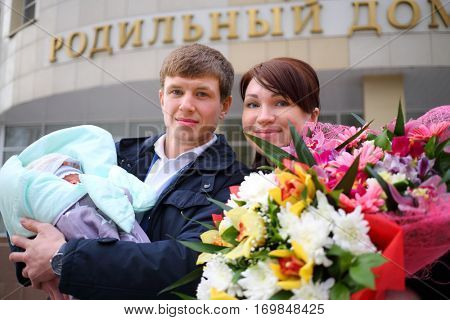 Man with newborn, woman with flowers stand near maternity hospital, text - maternity hospital