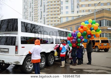 MOSCOW - MAR 22, 2016: Two Hummer limousine and people with balloons expecting newborn in Elk Island residential complex, Every year in Moscow, 143000 babies are born