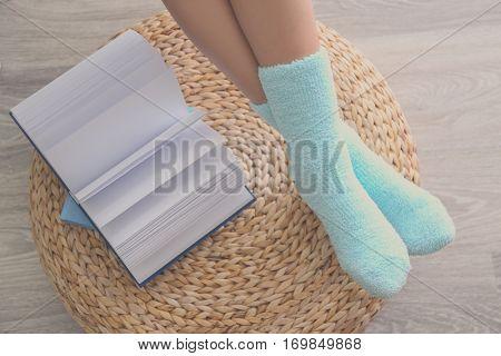 Human legs in knitted socks on ottoman beside open book
