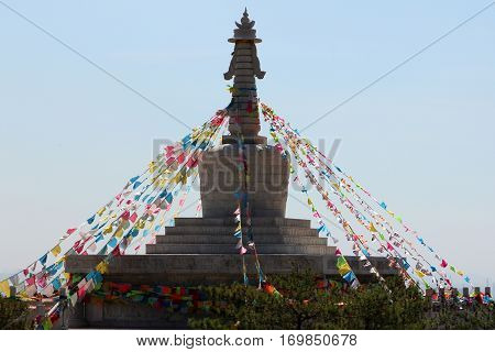 Buddhist stupa with prayers flags on top of hill Daqing mountains near Hohhot Inner Mongolia