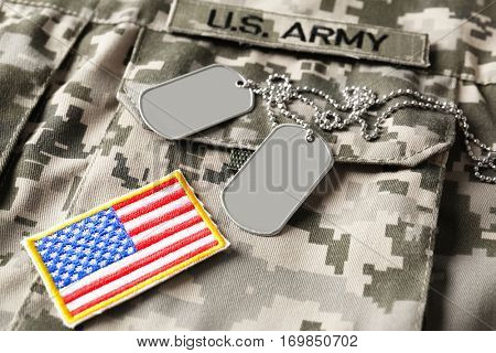 Army tokens and patches on military uniform background