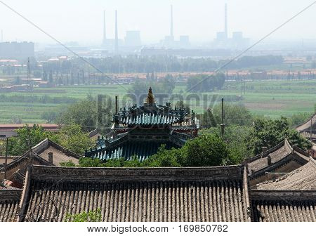 Ancient roof of Wusutu Zhao Buddhist Monastery on a background of modern Hohhot city Inner Mongolia
