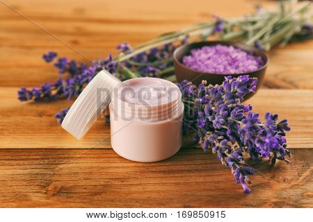 Nourishing cream and lavender flowers on wooden table, closeup