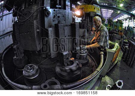 Tyumen, Russia - November 14, 2007: JSC Tyumenskie Motorostroiteli. Plant on production and repair of aviation engines. Elderly worker watches processing of detail on milling machine