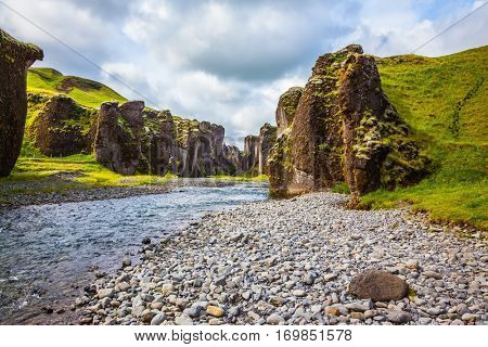 The concept of active northern tourism. Green Tundra in summer. The striking canyon in Iceland. Bizarre shape of cliffs surround the stream with glacial water