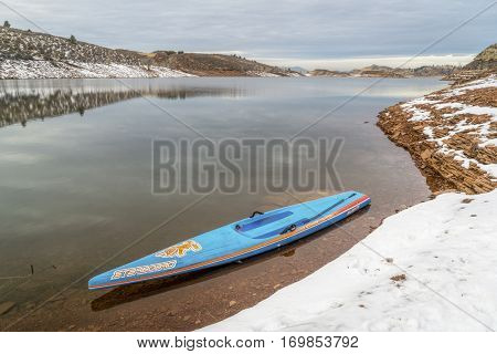 FORT COLLINS  CO, USA - DECEMBER 22, 2016: All Star racing stand up paddleboard by Starboard on a lake shore in winter scenery.