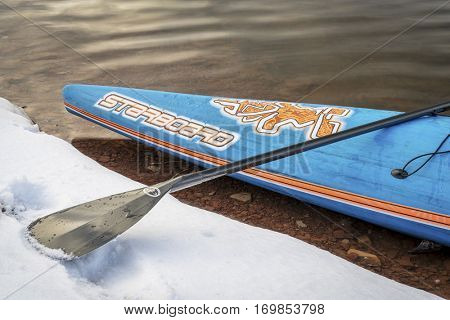 FORT COLLINS  CO, USA - DECEMBER 22, 2016: A bow of  All Star racing stand up paddleboard by Starboard with a paddle on a lake shore in winter scenery.