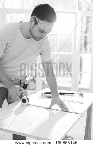 Mid-adult man marking table with measure tape