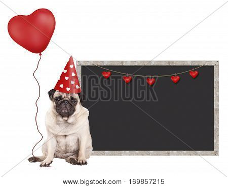 cute pug puppy dog with red party hat sitting next to blank blackboard sign and holding heart shaped balloon isolated on white background