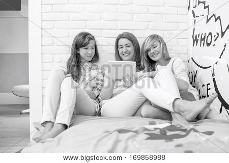 Mother with daughters using tablet PC in bedroom