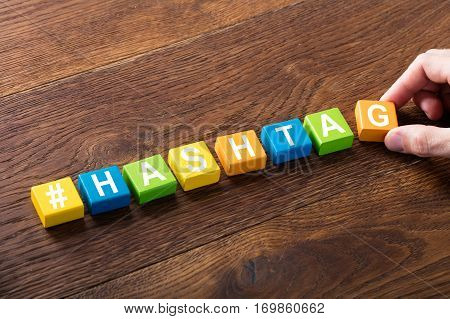 High Angle View Of A Person Hand Completing Hashtag Word Written On Colorful Cube Block