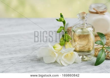 Spa still life with perfume and aromatic oil bottle surrounded by freesia flowers on light background