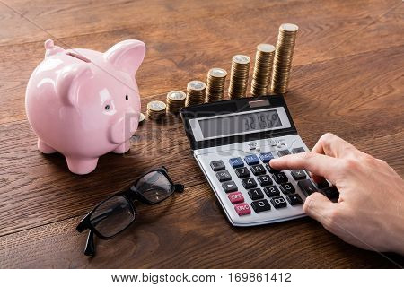 Person Calculating Savings On Calculator Using Piggybank And Stacked Coins On Wooden Desk
