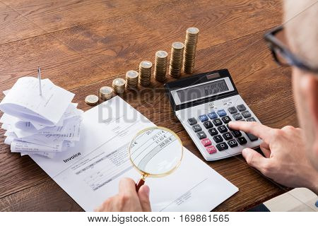 Auditor Hand Checking Invoice Using Magnifying Grass. Tax Fraud Investigation Concept poster