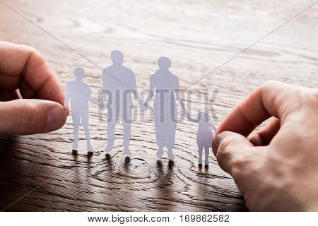Close-up Of A Person Holding Paper Cut Of Family On Wooden Desk