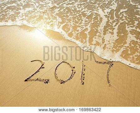 2017 written in sand write on tropical beach