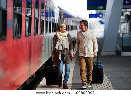 Beautiful senior couple on trainstation pulling a trolley luggage.