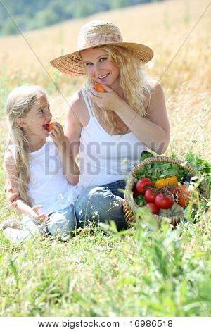 Mother and little girl eating fruits in garden