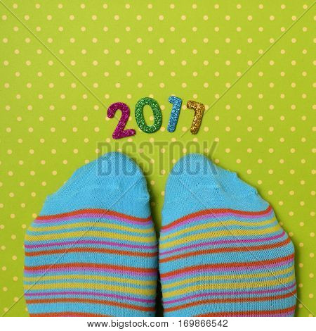 high-angle shot of a pair of feet wearing colorful striped socks and some glittering numbers of different colors forming the number 2017, as the new year, on a green surface patterned with white dots