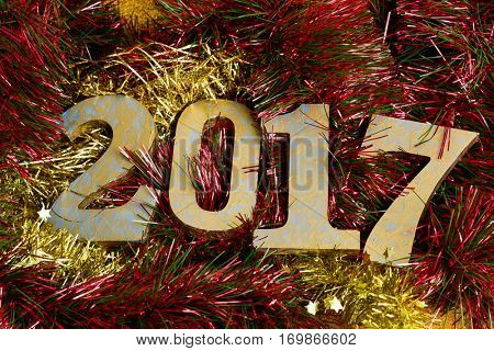 three-dimensional golden and blue numbers forming the number 2017, as the new year, on tinsel of different colors
