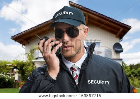 Close-up Of A Young Male Security Guard Using Walkie-talkie In Front Of A House