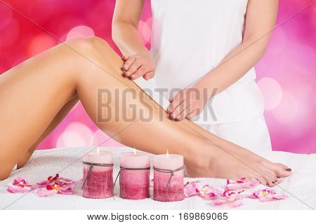 Close-up Of A Beautician Waxing Leg Of Woman With Wax Strip At A Beauty Spa