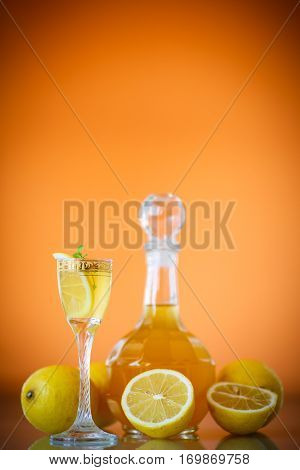 sweet lemon alcoholic brandy in the decanter on an orange background