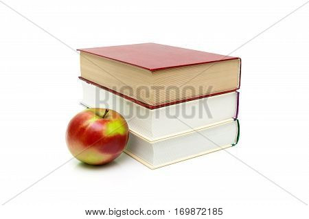 books and ripe apple on a white background. horizontal photo.
