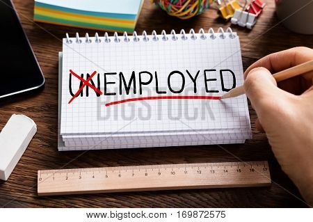High Angle View Of Person Hand Changing Unemployed To Employed On Notepad. Job And Employment Concept