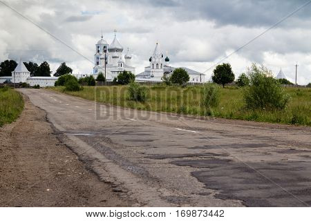 Pothole covered road in provincial Russia with white monastery at the background