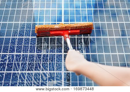 Close-Up Of Person Hand Cleaning Solar Panel. Sustainable Energy Concept